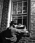 1950s THIEF MAN WEARING HAT GLOVES JACKET BREAKING INTO BRICK HOUSE OPENING WINDOW NIGHTTIME