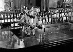 1940s 1950s MAN BARTENDER BEHIND BAR POURING A SHOT MIXING DRINK WEARING BOW TIE UNIFORM SHORT JACKET SET UP BOTTLES ON BACKBAR
