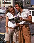 1970s 1980s HAPPY COUPLE MAN WOMAN SMILING READING TRAVEL BROCHURE MARINA VACATION