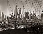 1950s SKYLINE LOWER MANHATTAN SEEN THRU CABLES OF BROOKLYN BRIDGE NEW YORK CITY NY USA