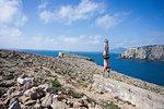 Man doing handstand on hilltop, Iglesias, Sardinia, Italy