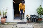 Woman in doorway beside wellies