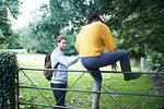 Hiker couple climbing over farm gate