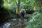 Hiker couple walking in stream
