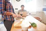 Woman preparing vegetables at kitchen table, boyfriend using laptop