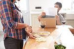 Woman preparing vegetables at kitchen table, boyfriend reading paperwork