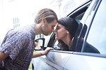 Romantic couple face to face through car window