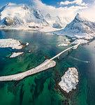 Aerial panoramic view of snowy peak of Volanstinden and Fredvang bridge, Lofoten Islands, Nordland, Norway, Europe