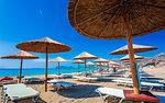 Umbrellas on the beach and emerald seas at Falassarna beach in Western Crete, Greek Islands, Greece, Europe