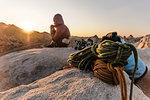 Rock climber on summit at sunset, Joshua Tree, California, USA