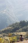Female hiker resting, enjoying sunny green foothills view, Supi Bageshwar, Uttarakhand, Indian Himalayan Foothills