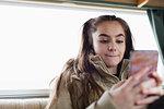 Teenage girl texting with smart phone