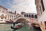 A traditional venetian gondola on Grand Canal, under Rialto Bridge, Venice, Veneto, Italy