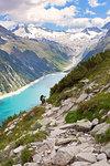 Hiking in Zillertal Alp, with Lake Schlegeispeicher and Hochfeiler group on the background, Tyrol, Schwaz district, Austria.