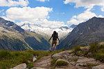 A hiker observes Hochfeiler group , Zillertal Alps, Tyrol, Schwaz district, Austria.