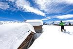 A trekker walks in the fresh snow with snowshoes near typical alpine huts. Wiesner Alp, Davos Wiesen, Landwasser Valley, Albula Valley, District of Prattigau/Davos, Canton of Graubünden, Switzerland, Europe.