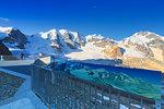 Tourist looks panorama from a panoramic terrace. Diavolezza Refuge, Bernina Pass, Engadin, Graubünden, Switzerland, Europe.