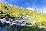 Hiker girl run across a pedestrian bridge. Unterer Segnesboden, Flims, District of Imboden, Canton of Grisons, Switzerland, Europe