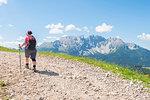 Hiker in front of Latemar, Val d'Ega / Eggental, Dolomites, Province of Bolzano, South Tyrol, italian alps, Italy