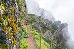 Woman walking on the trail from Pico Ruivo to Pico do Areeiro. Santana municipality, Madeira region, Portugal.