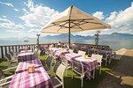 Tables of a little restaurant on the lakefront of Torri del Benaco on the eastern shore of Lake Garda, Verona province, Veneto, Italy.