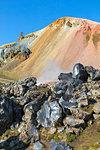 Rocks of the Laugahraun lava field and the Brennisteinsalda mountain on background from the Graenagil footpath in Landmannalaugar (Fjallabak Nature Reserve, Highlands, Southern Region, Iceland, Europe)