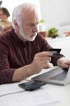 Focused senior man with credit card paying bills at laptop