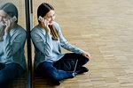Woman sitting cross legged by glass wall using cellphone