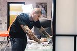 Tattooist using laptop in parlour