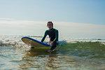 Surfer gliding on ocean wave, Watergate Bay, Cornwall, UK