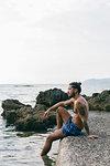 Man sitting on edge of sea
