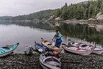 Woman with sea kayaks on lakeside, Johnstone Strait, Telegraph Cove, Canada
