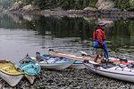 Man with sea kayaks on lakeside, Johnstone Strait, Telegraph Cove, Canada