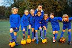 Portrait confident coach and girls soccer team
