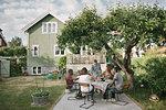 Multi-generational family enjoying drinks at patio during garden party
