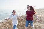 Playful lesbian couple running on sunny beach