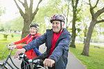 Active senior couple riding bikes in park