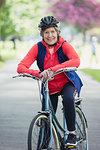 Portrait smiling, confident active senior woman riding bike in park