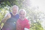 Portrait exuberant active senior men cheering in sunny park