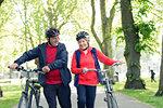 Active senior couple walking bikes in park