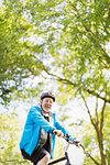 Portrait confident active senior man riding bike in park