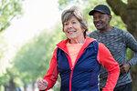 Smiling active senior woman power walking in park