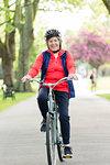 Portrait active senior woman riding bike in park