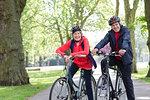Portrait smiling, confident active senior couple riding bikes in park