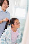 Mother fixing daughters hair in bathroom