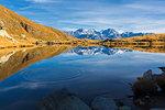 Peaks of Bernina Group reflected in the blue Lago Arcoglio during autumn, Valmalenco, Valtellina, Lombardy, Italy, Europe