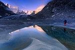 Hiker looks at sunrise from a pond at Forno Glacier, Forno Valley, Maloja Pass, Engadine, Graubunden, Switzerland, Europe