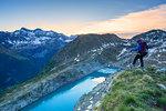 A hiker looks at Lake Pirola from above at sunrise, Chiareggio valley, Valmalenco, Valtellina, Lombardy, Italy, Europe