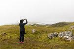 Woman taking photograph of Old Man of Storr through fog on Isle of Skye, Scotland