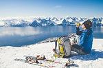 Skier sitting on snow in Lyngen, Norway